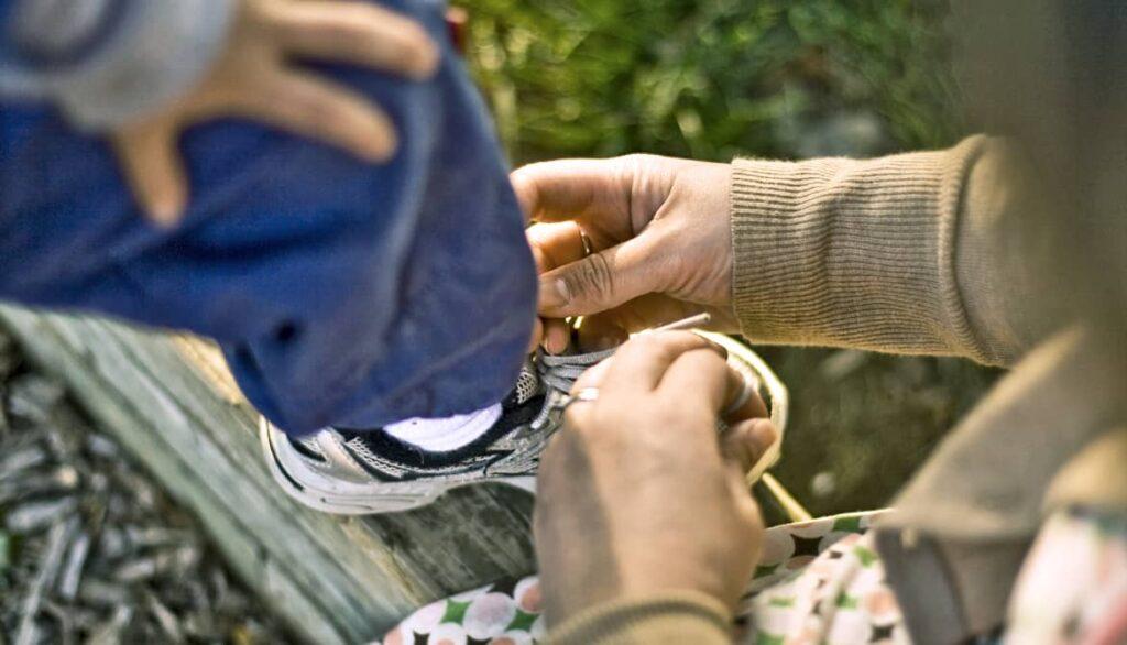 Madre ayudando a ponerse los zapatos a su hijo
