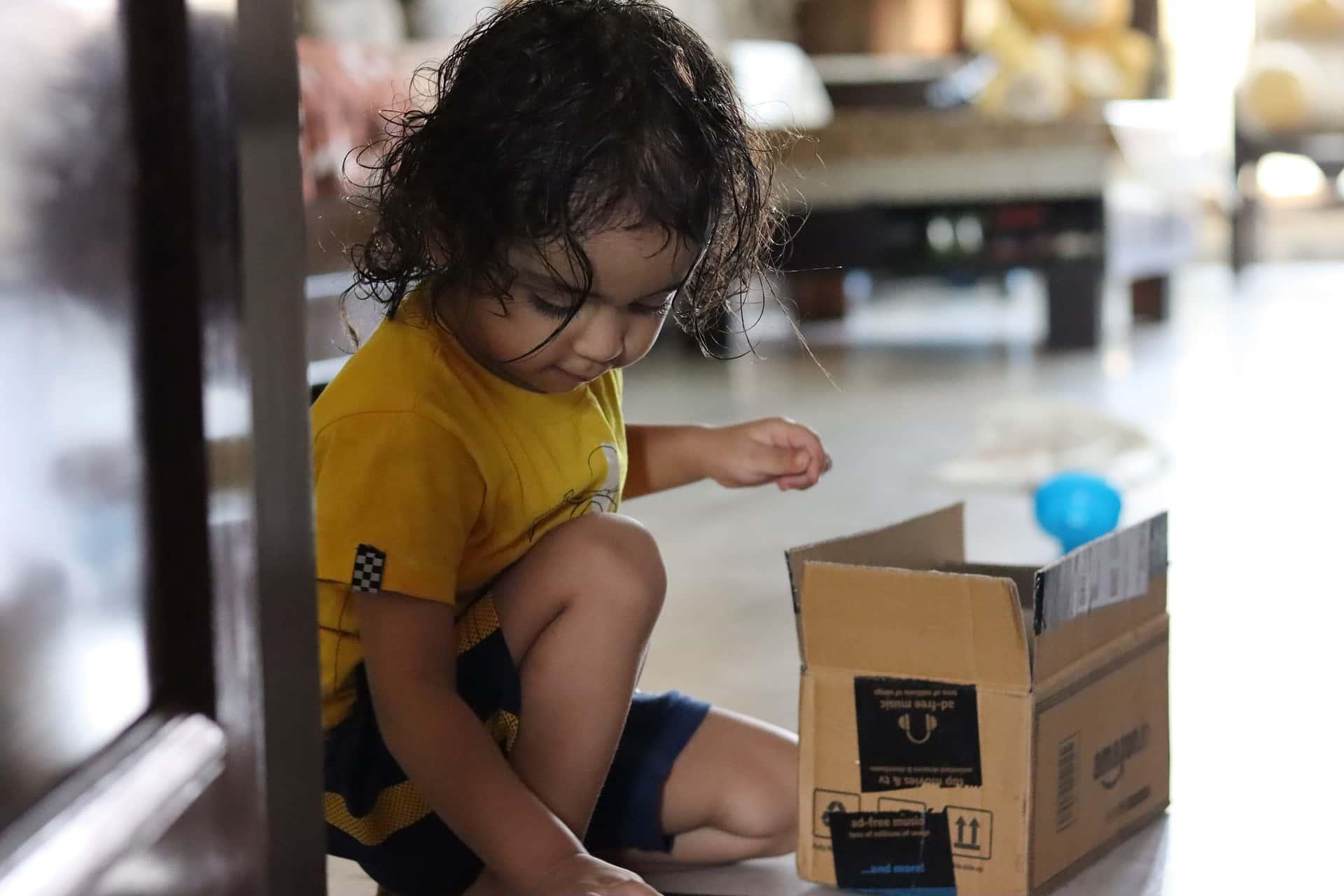 Niña jugando con caja de cartón