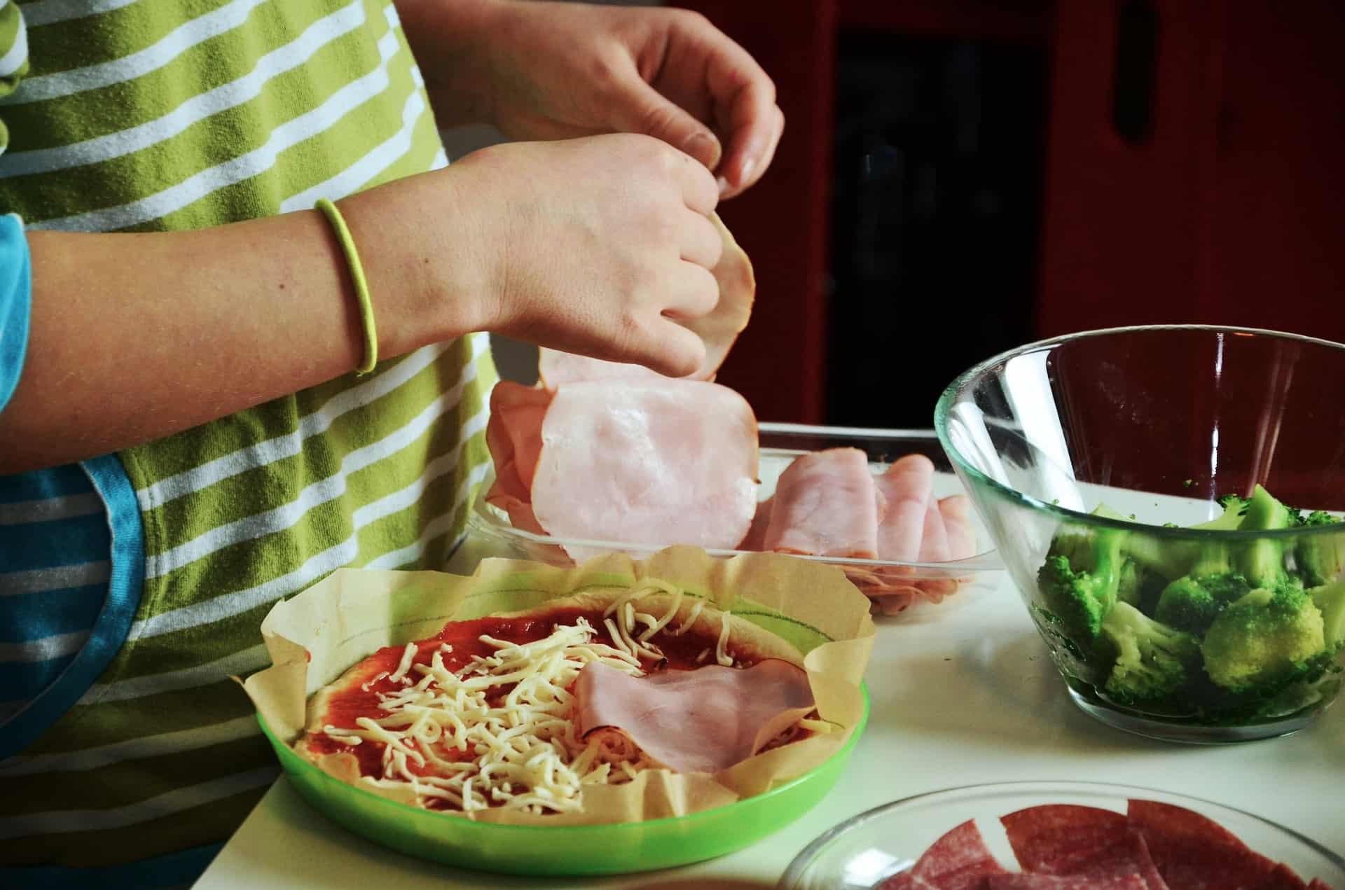 Niño cocinando una pizza